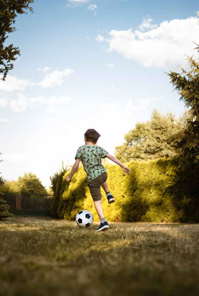 low angle photo of a boy playing soccer